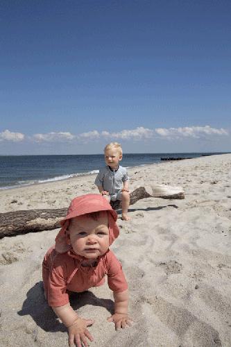 bébés sur la plage en vêtements anti UV